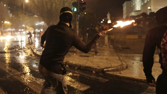 A protester throws a molotov cocktail at riot police during a 48-hour general strike in central Athens