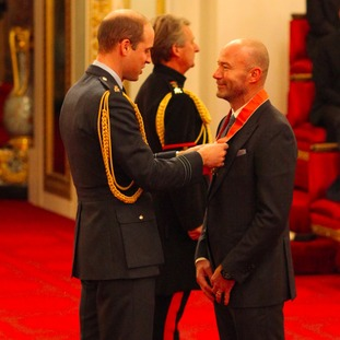 Alan Shearer receiving his CBE from Prince William.