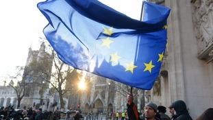 A man waves an EU flag outside the Supreme Court.