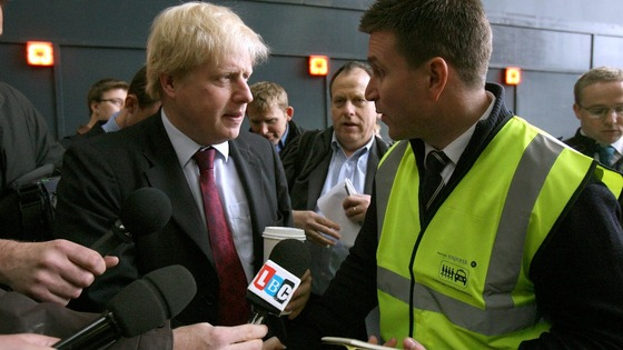 Mayor of London Boris Johnson speaks with a representative from the Paddington taxi share scheme.