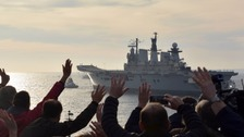 People wave as the Royal Navy's former aircraft carrier HMS Illustrious is towed out of Portsmouth Harbour heading for a Turkish scrapyard.