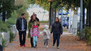 Reporter walks down the street with family in Finland