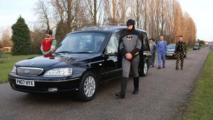 Pallbearers dressed as Batman and Robin