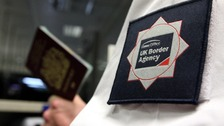 A UK Border Agency officer checking a passport in the North Terminal of Gatwick Airport, Sussex.