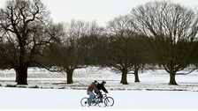 Cyclists ride through snow in Richmond Park.