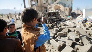 A child takes a picture of a bombed house.