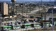 Residents gather near green government buses for evacuation from eastern Aleppo, Syria