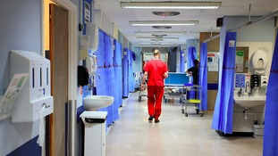 Man in scrubs walking down hospital ward