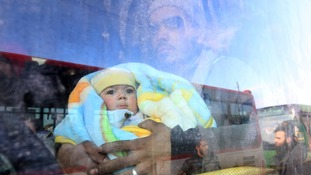 A man with a baby rides a bus to be evacuated from a rebel-held sector of eastern Aleppo