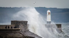 People watch waves crash over the harbour wall at Porthcawl, South Wales with the arrival of Storm Barbara.