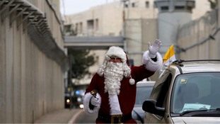 A Palestinian dressed as Santa Claus headed to the celebrations in the West Bank city of Bethlehem.