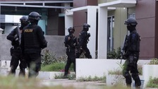 Indonesian anti-terror police enter a house during a raid Batam.