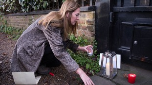 A woman lights a candle outside the singer's home.
