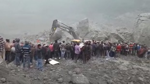 People gather at the scene as a digger works to clear rubble.