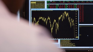 An office worker looks at a graph showing movement in the FTSE 100 Index.