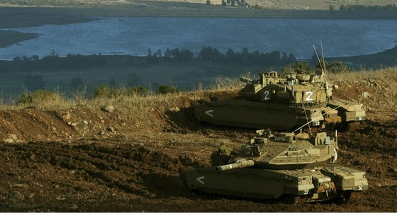 Israeli tanks stand in position overlooking a Syrian village from the Israeli occupied Golan Heights