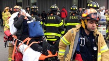 Woman being carried away on a stretcher after a train derailment in New York