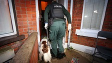 Officers carry out a drugs raid.