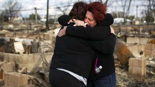 Neighbours Lucille Dwyer and Linda Strong embrace after looking through the wreckage of their homes