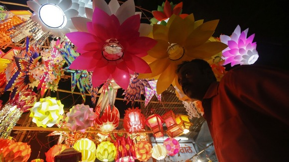 A man stands under lanterns for sale at a market in Mumbai on the eve of Diwali