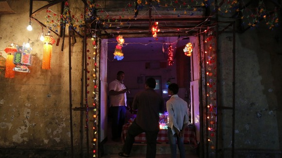 People enter a shop decorated with lights at a market in Mumbai