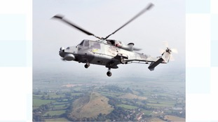 A Royal Navy Wildcat helicopter in flight over Glastonbury Tor