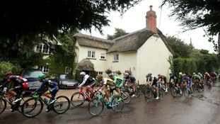 The Peloton passes a thatched cottage in the village of Wiggaton during stage six of the 2016 Tour of Britain between Sidmouth to Haytor