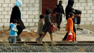 People from the northern Syrian town of Ras al-Ain walk along a train track as they attempt to cross into Turkey.