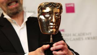 A winner's BAFTA mask is held aloft.
