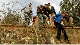 Syrian refugees try to cross border fence from northern Syrian town of Ras al-Ain to Turkey during an air strike