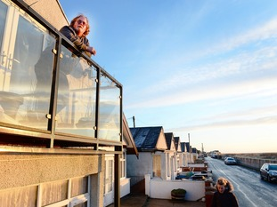 Phil Squire looks out from his balcony on Brooklands Road in Jaywick, Essex.