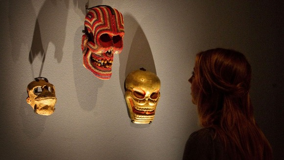 A visitor looks at masks which make up part of the collection