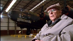 John Evans sat in an aircraft hangar with halifax plane in the background