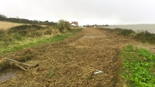 The coast road at Salthouse covered in debris from the storm surge