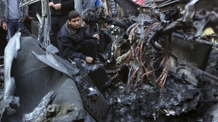 A policeman checks the destroyed car of Hamas's military chief following an Israeli air strike in Gaza City