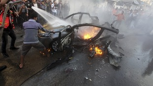 Palestinians help extinguish the fire on the car of Hamas's top commander after an Israeli airstrike