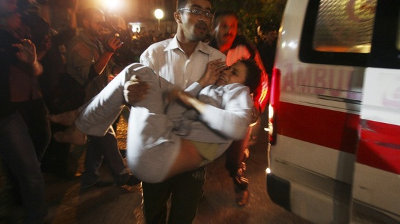 A wounded woman is carried into a hospital after Israeli air strikes in Gaza City