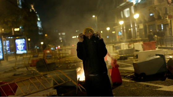 A protester stands next to a burning garbage container during a 24-hour nationwide general strike in central Madrid