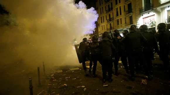 Spanish police officers advance through the smoke from a flare during a 24-hour nationwide general strike in central Madrid