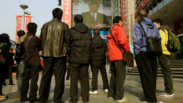 People watch a screen showing newly-elected General Secretary of the Central Committee of the Communist Party of China Xi Jinping