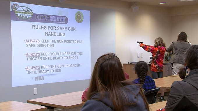 Girl Scouts being taught how to fire a gun