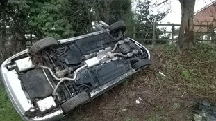 Lucky escape for two after car hits tree and ends up on its side