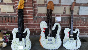 Wreaths shaped as guitars were laid to remember Mr Parfitt.