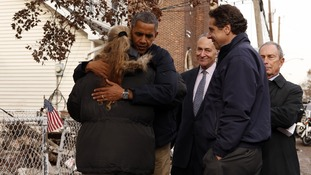 US President Barack Obama hugs resident Debbie Ingenito as he tours a hurricane battered Staten Island