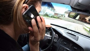 Girl using mobile phone behind the wheel