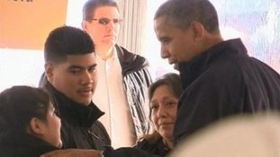President Obama meets a family at an aid distribution tent in New York