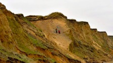 Two walkers climb the crumbling cliffs at West Runton in Norfolk.