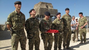 British soldier lays wreath of flowers during Britain's Veterans Day ceremony at a NATO base