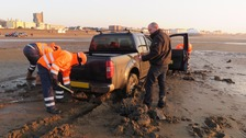 Stranded car stuck in the mud on Burnham beach