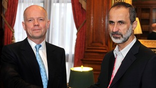 Foreign Secretary William Hague shakes hands with President Sheikh Ahmed Mu'az Al-Khatb of the Syrian opposition movement.